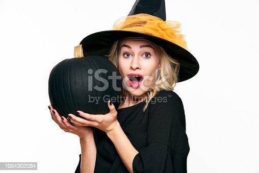 512061362 istock photo Halloween Witch with shocked expression holding large black pumpkin. Beautiful young woman in witches hat and costume holding pumpkin over white background. 1054302034