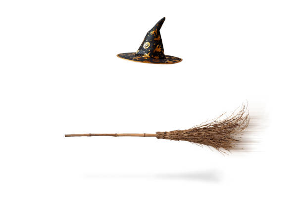 Halloween witch's hat and broom isolated stock photo