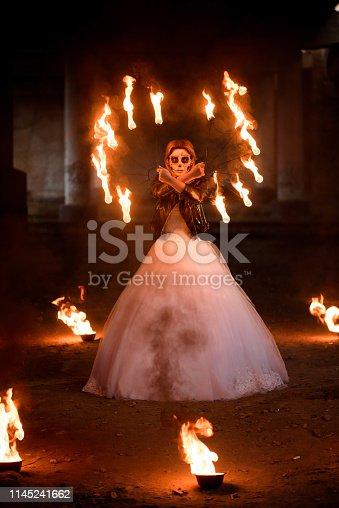 512061362istockphoto Halloween. Young beautiful girl with make-up skeleton 1145241662