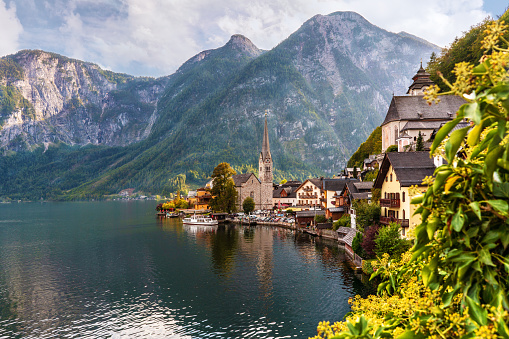 Hallstatt iconic view: Alpine mountains, lake, and picturesque village with evangelic church.