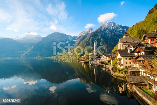 Scenic nature landscape view of Hallstatt mountain village reflecting in Hallstatter see lake against The Austrian Alpines in with morning sunshine and beautiful blue cloudy sky looking like a postcard picture in Salzkammergut region, Austria xxxl size april 2017