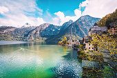 Panoramic view of Scenic nature landscape view of Hallstatt mountain village reflecting in Hallstatter see lake against The Austrian Alpines in with morning sunshine and beautiful blue cloudy sky looking like a postcard picture in Salzkammergut region, Austria xxxl size april 2017