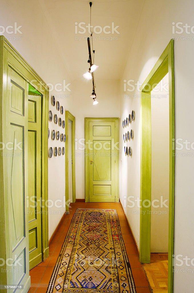 Hallway of elegant house, wooden doors, persian carpet, hanging dishes stock photo
