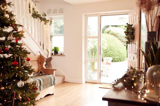 flur des hauses dekoriert für weihnachten in richtung offener haustür - deko hauseingang weihnachten stock-fotos und bilder