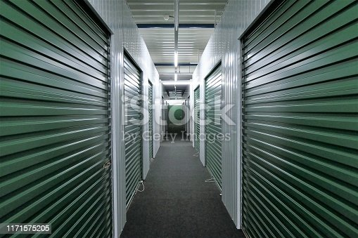 hallway of self storage units for rent with green rolling doors
