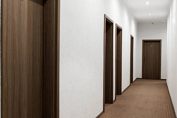 korridor mit verschlossenen türen - eingangshalle wohngebäude innenansicht stock-fotos und bilder