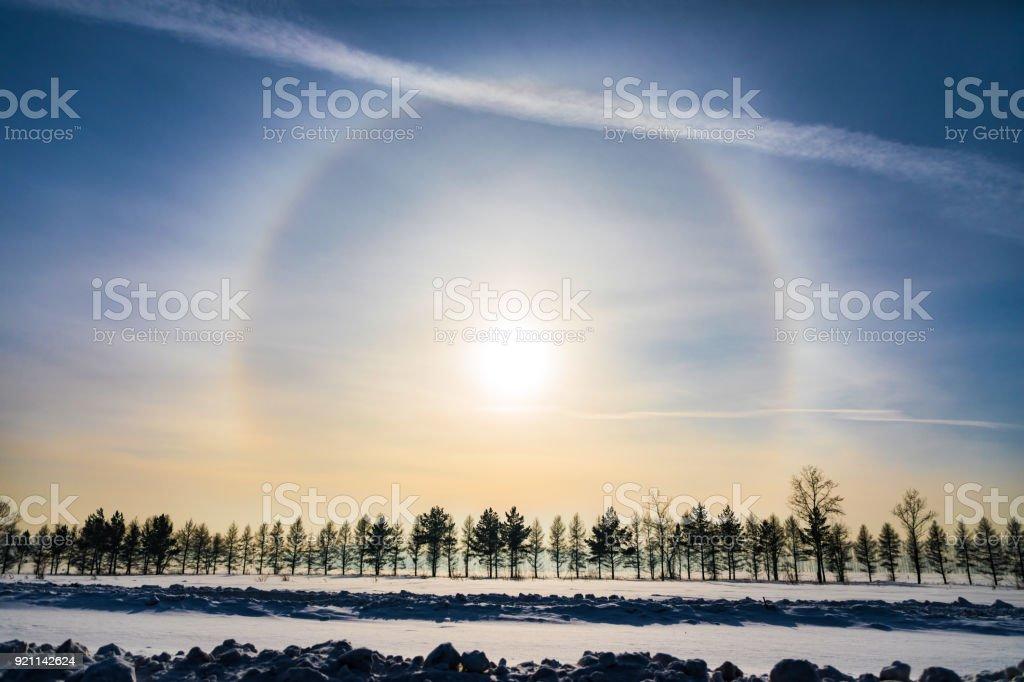 Halo around sun on blue sky in winter time stock photo