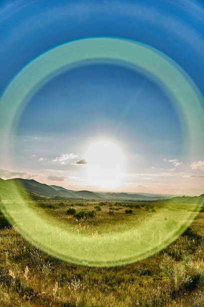 Halo effect around the sun with round rays - beautiful landscape of steppe and stone mountains along the road from the city of Ust-Kamenogorsk to the Sibiny lakes (Sibinskiye Ozora), East Kazakhstan stock photo