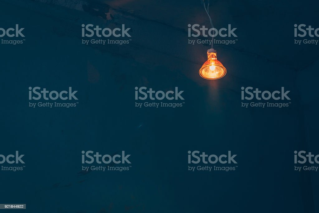 Halogen bulb with warm light in a dark room, dim light, copy space