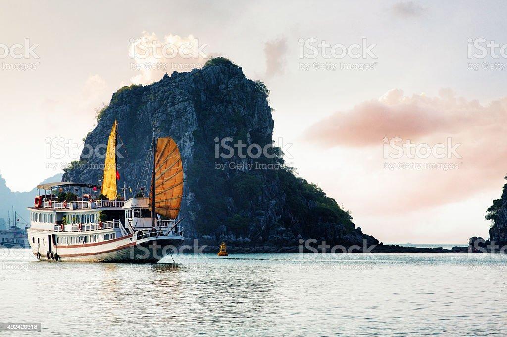Bahía de Halong Vietnam tourist ship con acantilado island en puesta de sol - foto de stock
