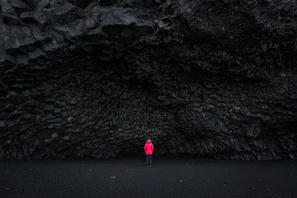 Halsanefshellir Cave on a Black Sand Beach Iceland A woman in a red coat is used for scale and contrast against the black sand beach cave near Vik Iceland. black sand stock pictures, royalty-free photos & images