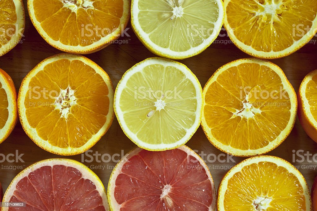 Halve citrus fruits on cuttting board royalty-free stock photo