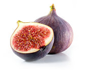 A halved and whole fig isolated on a white background