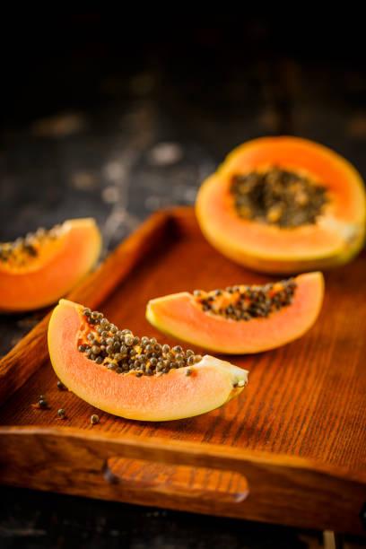 Halbierte und ganze Papaya-Früchte auf dem Hintergrund – Foto