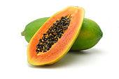 Halved and whole papaya fruits on white background