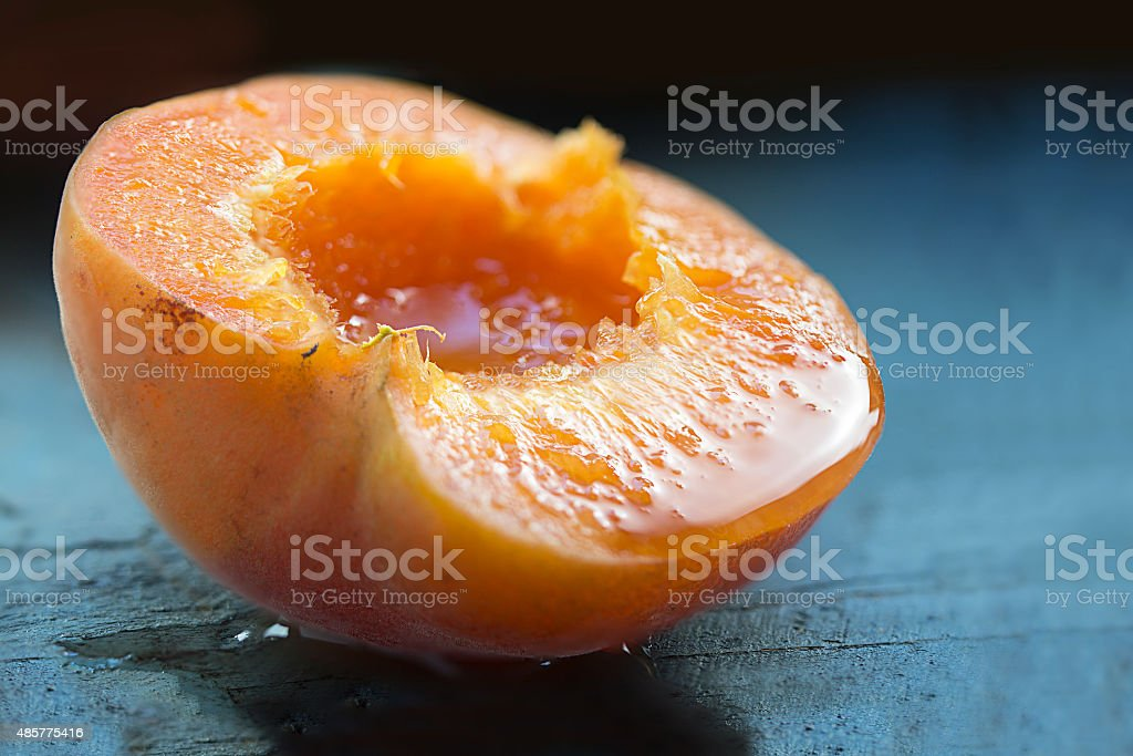 halved apricot, ripe and juicy on blue wood, closeup stock photo