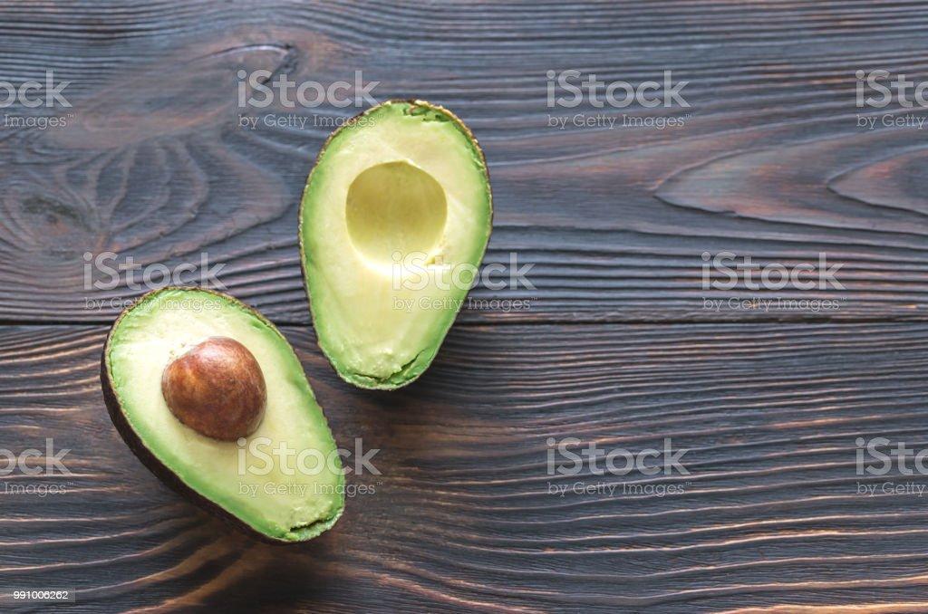 Abacate cortados ao meio no fundo de madeira - foto de acervo