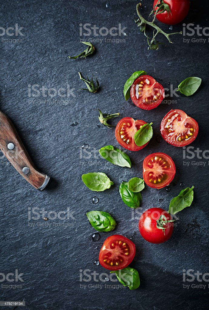Halved cherry tomatoes and basil leaves on black slate stock photo
