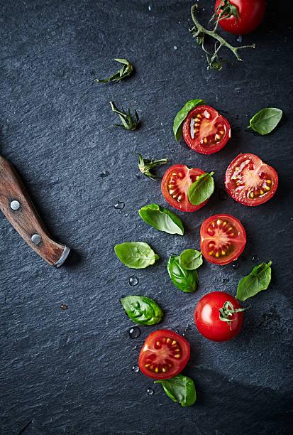 Um die Hälfte geschrumpft cherry-Tomaten und Basilikum auf schwarze Tafel – Foto