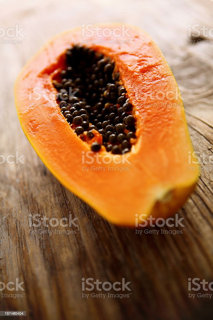 A halved fresh papaya on a wooden surface stock photo