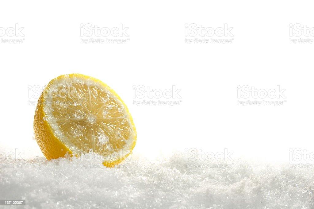 Halved lemon on white grainy ice stock photo