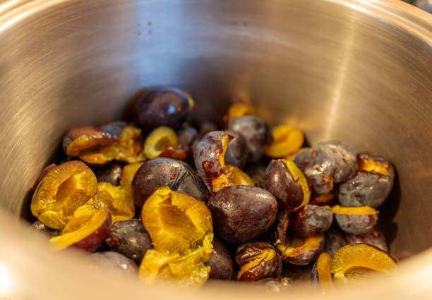 halved pitted plums ready for jam cooking stock photo
