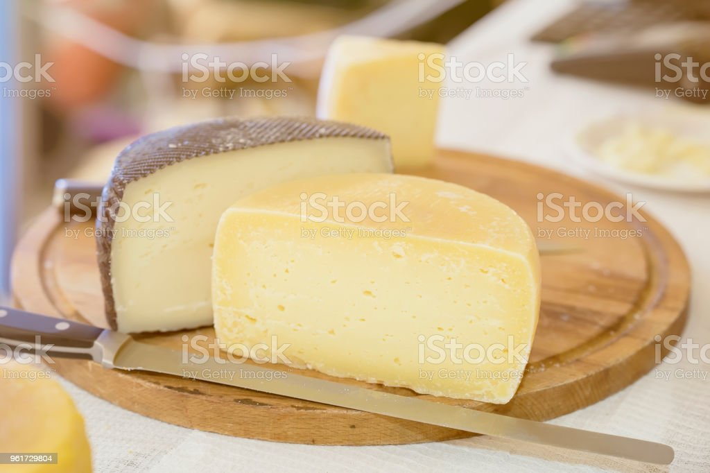 Halves hard cheese heads on wooden market board. Gastronomic dairy produce, real scene in the food market stock photo