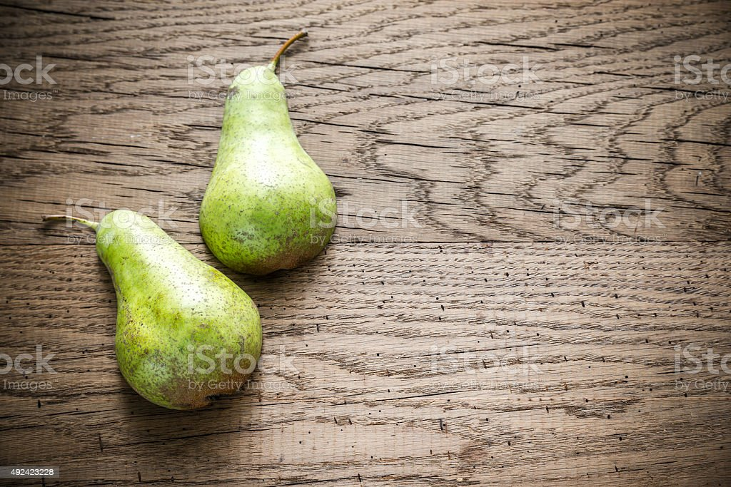 Halves of green pear on the wooden background stock photo
