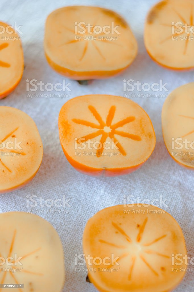 Halves of persimmon fruit on fabric material. photo libre de droits
