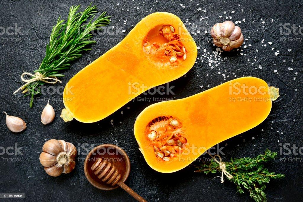 Hälften der Rohe organische Butternut-Kürbis mit Gewürzen und Zutaten für die Herstellung – Foto