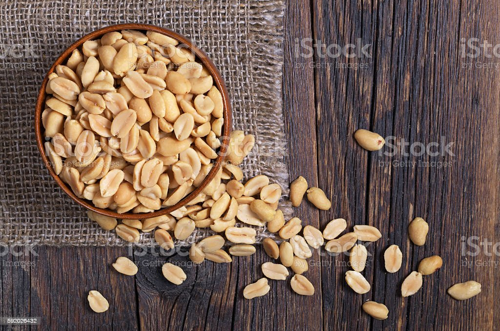 Halves of roasted peanuts Halves of roasted peanuts in bowl and near on dark wooden background, top view Close-up Stock Photo