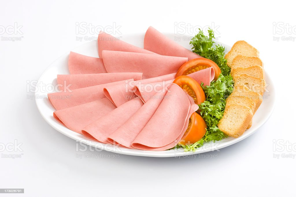 Ham and bread with lettuce and tomato in between them royalty-free stock photo