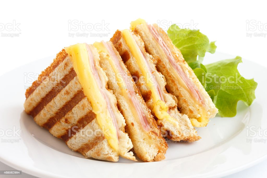Ham and cheese sandwich in a plate with lettuce on the side  stock photo
