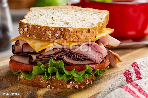 Ham sandwich with cheese, tomato and lettuce on whole grain bread on a wooden cutting board
