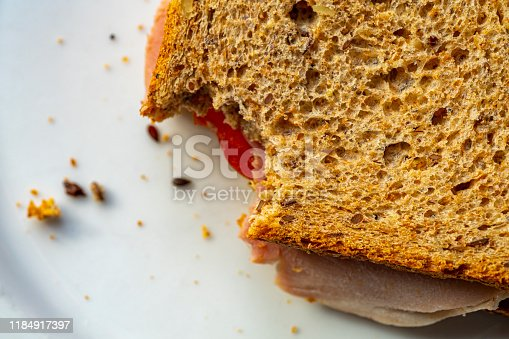 Extreme close-up of a ham and tomato sandwich on a plate with a bite taken out.