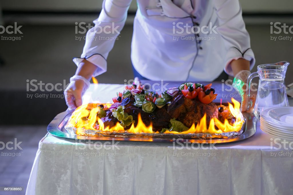 ham cooking on grill with flames. Dish served with fire chef on background stock photo