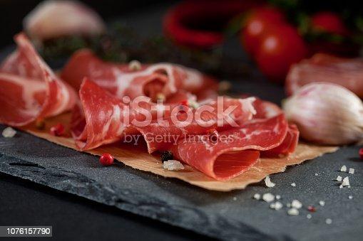 istock Ham on black stone slate board. 1076157790