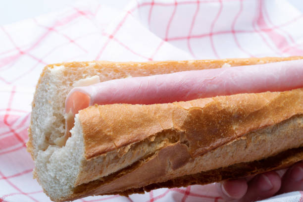 ham sandwich with a French baguette and tea towel in the background stock photo