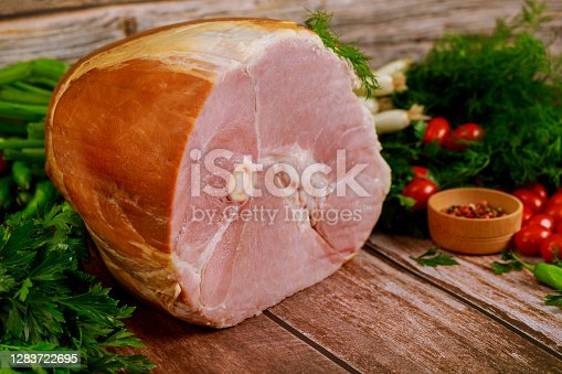 Ham with fresh dill, chive and tomato on wooden rustic table.