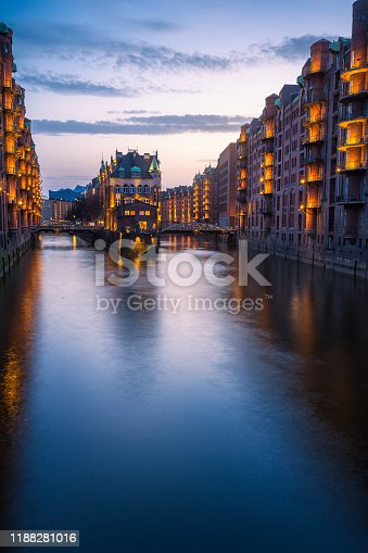 Hamburg city old port during blue hour, Germany, Europe. Historical famous warehouse district artificial illuminated. Water castle palace mirrored on river surface. Vertical orientation.