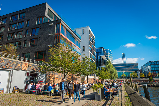 Hamburg crowds enjoying sunshine outdoor restaurants HafenCity waterfront promenade Germany