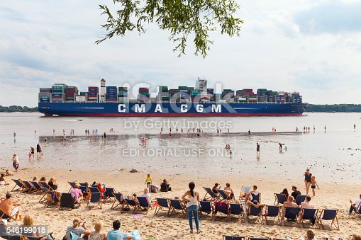 Hamburg, Germany - July 10, 2016: Container ship passing the beach of Wedel, Hamburg. Many people enjoy the warm summer afternoon, observing the huge container ship.