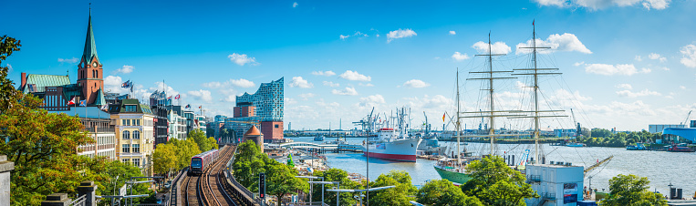 Panoramic view across the waterfront of central Hamburg, from the villas of Landungsbrucken past the iconic edifice of the Elbphilharmonie to the ships in the busy harbour of the Port of Hamburg, Germany.