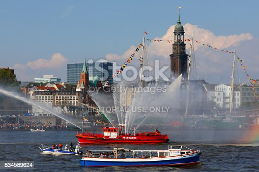 Hamburg, Germany - May 07, 2017: Hamburg harbor birthday celebration (Hafengeburtstag). One million visitors from around the world joined the world's greatest port festival. Fire-fighting boat announces the beginning of the final ship-parade. Michel Church (Michaelis Church) and the tall ship Rickmer Rickmers in the background.