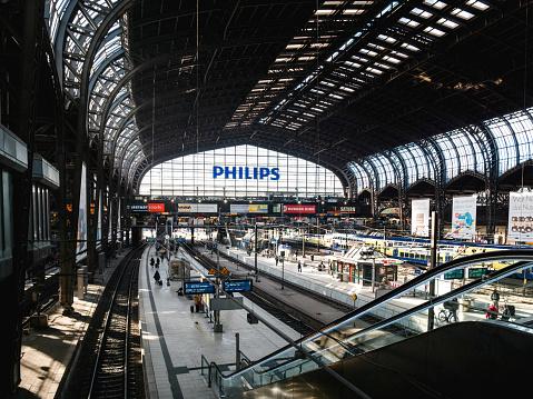 Hamburg: Hamburg Hauptbahnhof wide interior with elevated view of trains, people traveling and huge Philips advertisement