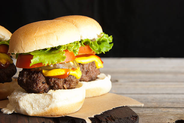 """Hamburger Sliders """"Three hamburger sliders with lettuce, tomatoes, pickles, mustard and ketchup on a rustic cutting board and table.Similar Images:"""" slider burger stock pictures, royalty-free photos & images"""