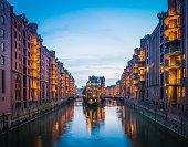 Hamburg Speicherstadt iconic canal warehouses warmly illuminated at dusk Germany