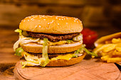 Hamburger and french fries on rustic wooden table