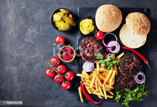 Hamburger Building Kit - freshly baked buns, fried beef burgers, pickles, ketchup, mustard, onion rings, tomatoes and french fries on a slate tray, view from above, flatlay, empty space