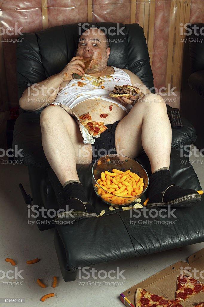 Hamburger eating lazy couch potato stock photo